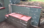 Repaired leaning retaining wall and a block bench.